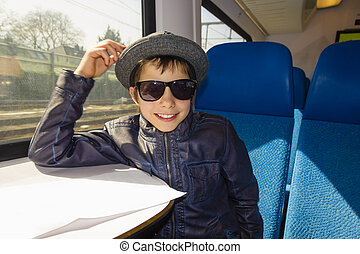 Handsome boy with sunglasses rides on a train reading from the paper