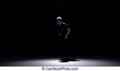 Handsome breakdance style dancer starts dance, on black,...
