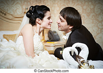 Handsome bride and groom in bedroom