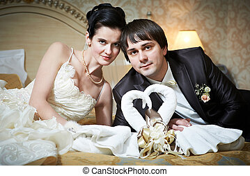 Handsome bride and groom in bedroom with towels swans