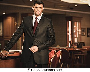 Handsome brunette wearing suit and necktie in luxury...