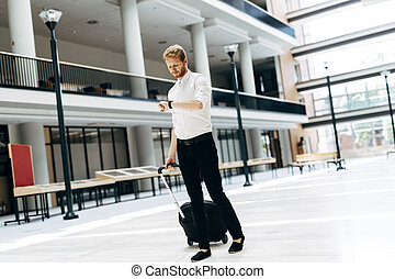 Handsome business holding a trolley