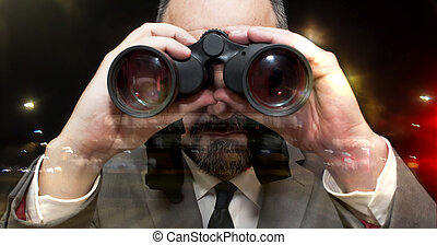 Handsome business man, bald and beard, looking through binoculars through a window into the city at night