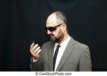Handsome business man, bald and beard,  with sunglasses looking at his mobile phone over black