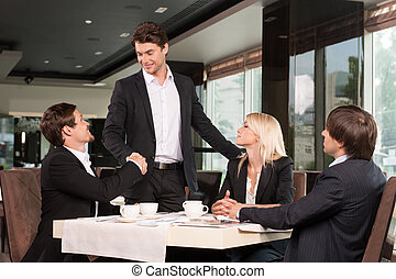 Handsome business man greeting group of people. Sitting at restaurant drinking coffee