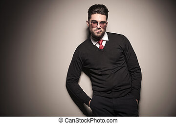 Handsome business man leaning on a grey wall with his hands...