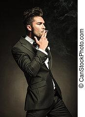 Handsome business man smoking a cigarette