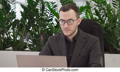 Handsome business man using a laptop looking at camera and smiling