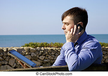 Handsome business man working with tablet and phone outdoor
