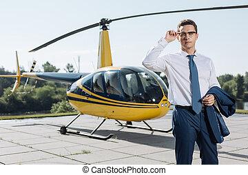 Handsome businessman adjusting glasses before taking helicopter