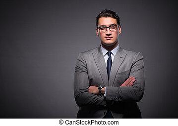 Handsome businessman against dark background