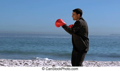 Handsome businessman boxing on the beach  in slow motion