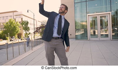 Handsome businessman celebrating and doing a crazy dance to the camera