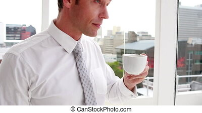 Handsome businessman drinking coffee and looking out window in the office