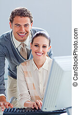 Handsome businessman helping his colleague work at a computer