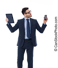 Handsome businessman holding in his hands digital tablet and mobile phone