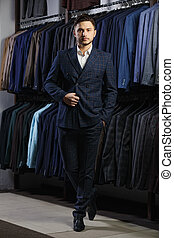 Handsome businessman in classic suit. A young stylish man in a jacket. It is in the showroom, trying on clothes, posing. Advertising photo