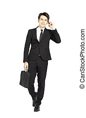 Handsome businessman in suit and speaking on the phone