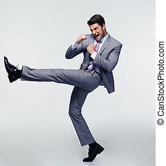 Handsome businessman kicking
