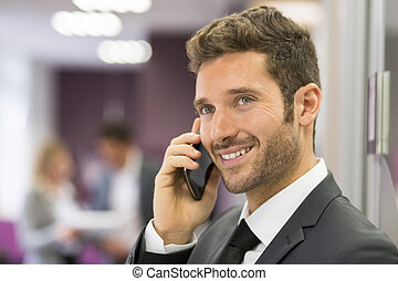 Handsome businessman on mobile phone in modern office