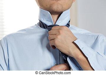 Handsome businessman preparing to official event, straighten...