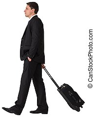 Handsome businessman pulling his suitcase