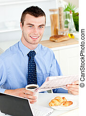 Handsome businessman reading the newspaper drinking coffee