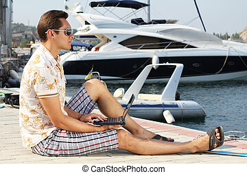 Handsome businessman running a laptop on the shore near the yacht boat at rest