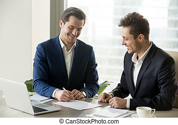 Handsome businessman signing contract with partner