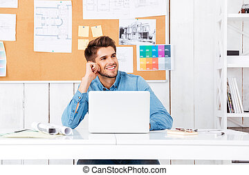 Handsome businessman sitting at his workplace and talking on phone