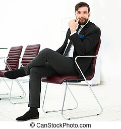 handsome businessman sitting on a chair in a conference room