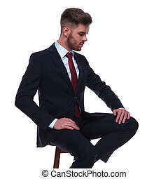 handsome businessman sitting on chair looks down to side