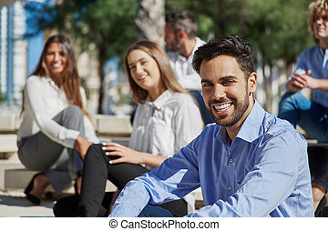 Handsome businessman sitting with coworkers outside smiling