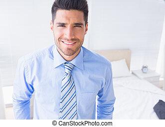 Handsome businessman smiling at cam