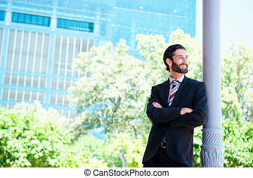 Handsome businessman smiling in the city