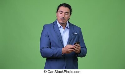 Handsome businessman smiling while using phone