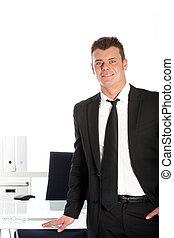 Handsome businessman standing at his desk