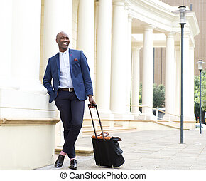 Handsome businessman standing outdoors with bag