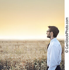 Handsome businessman staring at the sunset