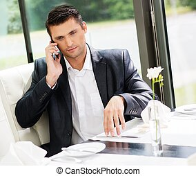 Handsome businessman talking over mobile phone in restaurant