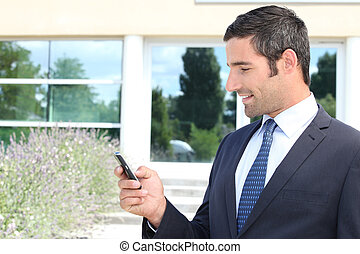 Handsome businessman texting on a mobile phone