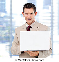 Handsome businessman using a laptop standing