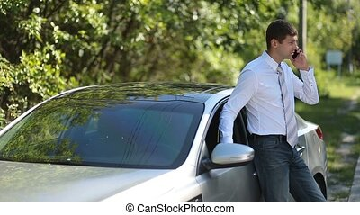 Handsome businessman using mobile phone near car