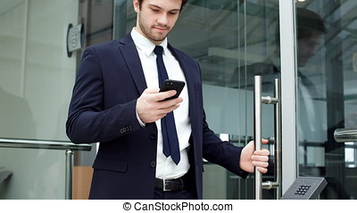 Handsome Businessman Using Smartphone in The Office.
