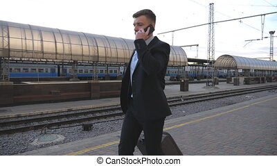 Handsome businessman walking through railway station with...