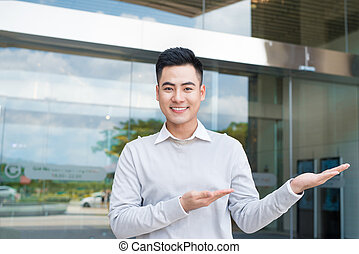 Handsome businessman with arm out in a welcoming gesture