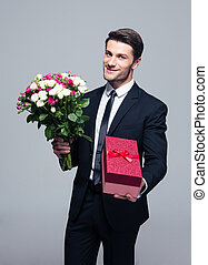 Handsome businessman with flowers and gift box