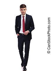 handsome businessman with hand in pocket stepping forward