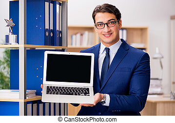 Handsome businessman with laptop in the office