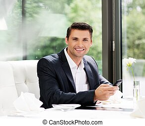 Handsome businessman with mobile phone in restaurant